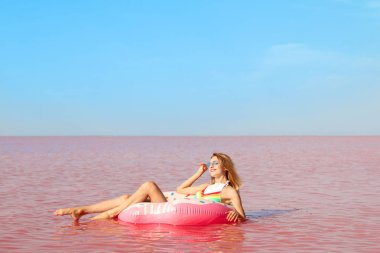 Beautiful woman on inflatable ring in pink lake