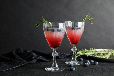 Glasses of refreshing blueberry cocktail with rosemary on table