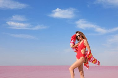 Beautiful woman in swimsuit posing near pink lake on sunny day