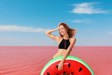 Beautiful woman with inflatable ring posing near pink lake on sunny day