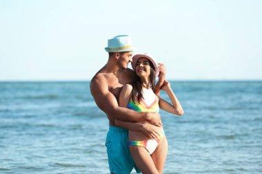 Happy young couple posing near sea on beach
