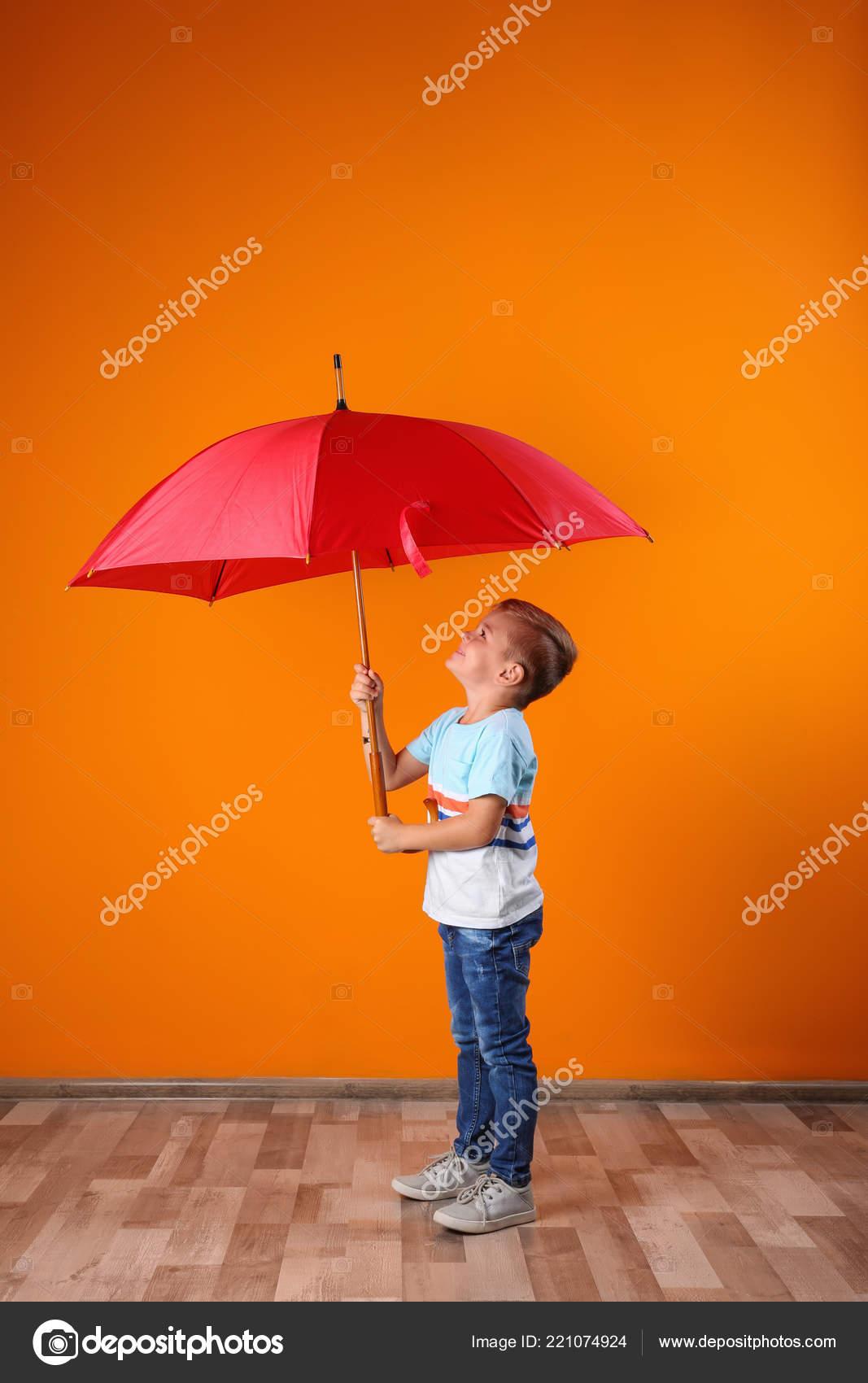 Couleur Avec Du Rouge petit garçon avec parapluie rouge près mur couleur