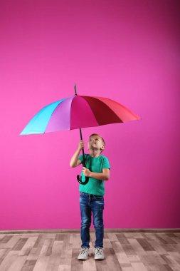 Little boy with rainbow umbrella near color wall