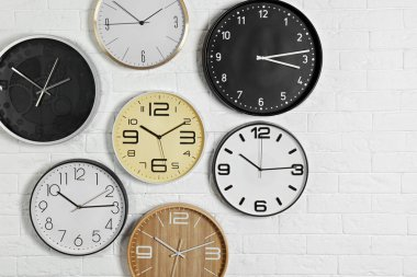 Different analog clocks hanging on white wall. Time of day