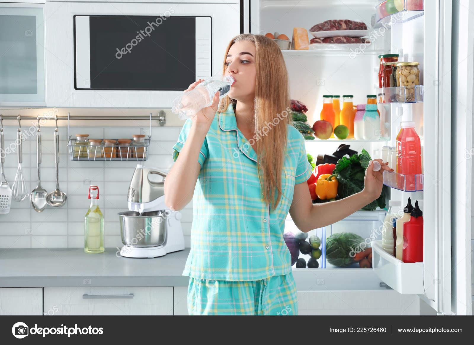 Kühlschrank Deo : Frau trinkwasser aus der flasche der nähe von kühlschrank der