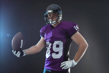 American football player with ball on dark background