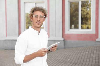 Male real estate agent with tablet outdoors, space for text