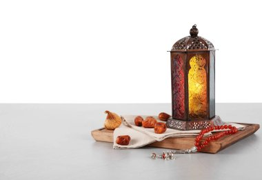 Muslim lamp, dates and prayer beads on table against white background. Space for text