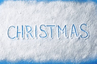 Word CHRISTMAS written in snow on color background, top view