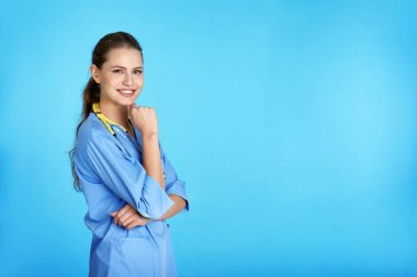 Portrait of young medical assistant with stethoscope on color background. Space for text