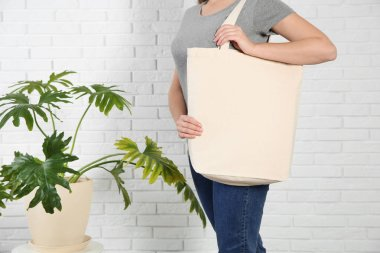 Woman with eco bag and green plant near brick wall. Mock up for design