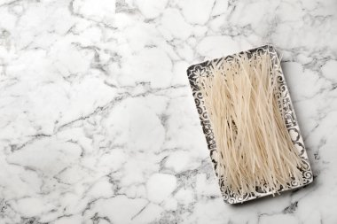 Plate with raw rice noodles on marble background, top view. Space for text