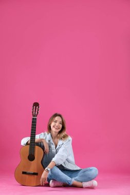 Young woman with acoustic guitar on grey background. Space for text