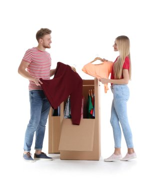 Young couple near wardrobe boxes on white background