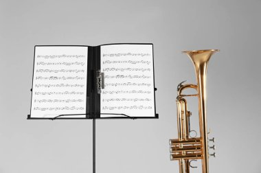 Trumpet, chair and note stand with music sheets on wooden wall background
