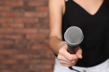 Young woman holding microphone near brick wall, closeup view with space for text