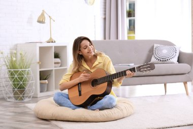 Young woman playing acoustic guitar in living room