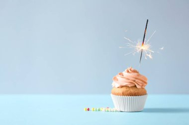 Delicious orange cupcake with burning sparkler on table against light background. Space for text