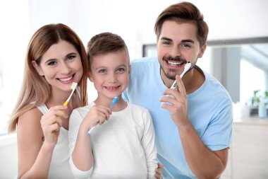 Portrait of happy family with toothbrushes in bathroom. Personal hygiene