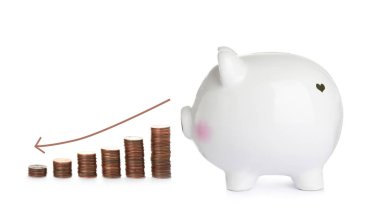 Ceramic piggy bank and coins on white background