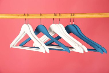 Empty clothes hangers on wooden rail against color background