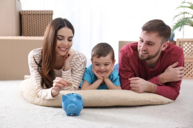 Happy family with piggy bank and money on floor at home