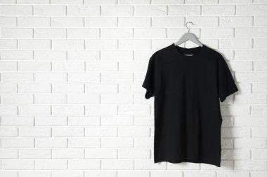 Hanger with black t-shirt against brick wall. Mockup for design
