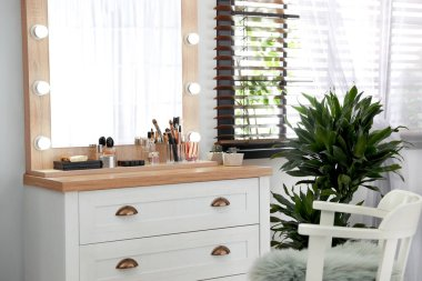 Dressing table with luxury cosmetics and accessories in room near window