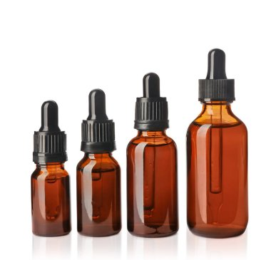 Cosmetic bottles of essential oils on white background