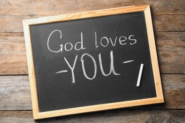 Chalkboard with words GOD LOVES YOU on wooden background, top view
