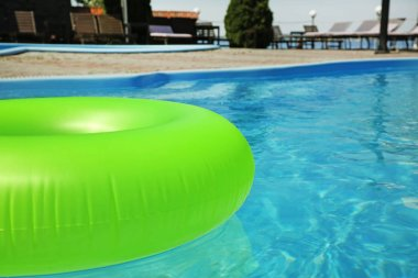 Bright inflatable ring floating in swimming pool on sunny day, outdoors. Space for text