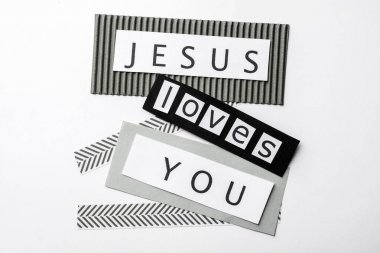 Printed words JESUS LOVES YOU on white background, top view
