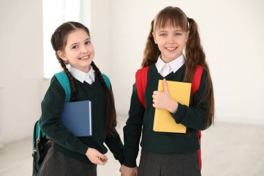Portrait of cute girls in school uniform with backpacks and books indoors