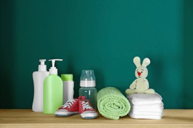 Bathroom accessories and toy for baby room interior on wooden table near turquoise wall