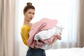 Frau hält Haufen von schmutzigen Wäsche in Innenräumen