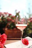 Glas Rosenwein auf dem Tisch im blühenden Garten