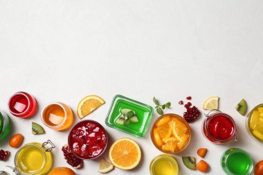 Flat lay composition with different jelly desserts on light background, space for text