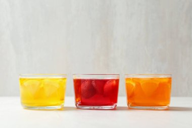Glass bowls of natural jelly desserts on light table, space for text