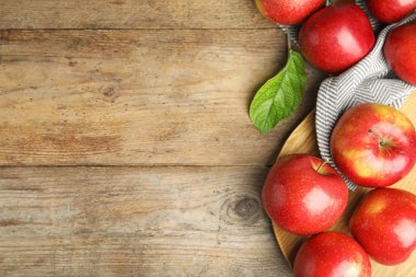 Ripe juicy red apples on wooden background, flat lay. Space for text