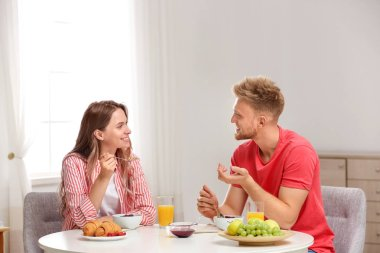 Happy young couple having breakfast at table in room