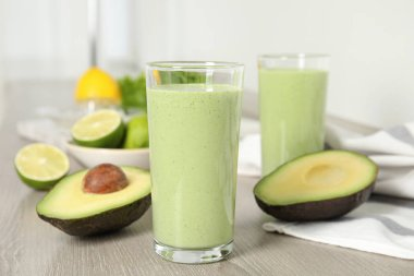Glasses of tasty avocado smoothie and ingredients on wooden table