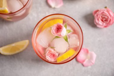 Tasty refreshing lemon drink with roses on light grey table, top view