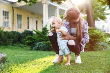 Teen nanny with cute baby on green grass outdoors. Space for text