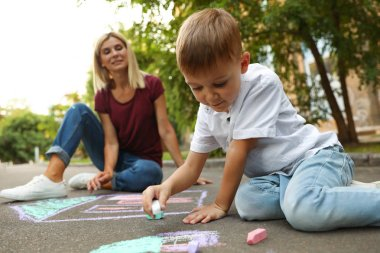 Nanny with cute little boy drawing house with chalks on asphalt