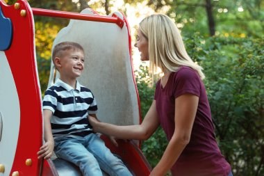 Nanny and cute little boy on slide outdoors