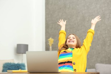 Happy young woman playing online lottery using laptop at home