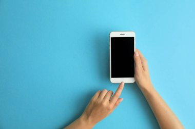 Woman holding modern phone on blue background, top view. Space for text