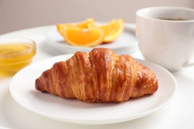 Delicious breakfast with croissant and honey on white table, closeup