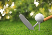 Golfový míč s klubem na zeleném hřišti