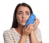 Junge Frau leidet Zahnschmerzen auf weißem Hintergrund